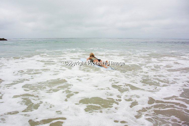 Woman going out to sea to find a surfing wave