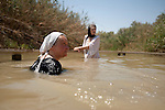 Christian pilgrims in the Jordan River, at the baptism site of Qasr el-Yahud, near Jericho, Jordan Valley, West Bank. The site is traditionally believed to be the place where Jesus was baptized.