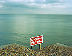 A sign on a groyne - breakwater - warns of a steep drop onto a lower section of beach on the shore of Brighton beach on the South coast of England.<br /> [This photograph is currently licensed through GalleryStock - please contact the photographer for details]