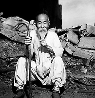 An old Korean man takes a rest on the street in front of destroyed buildings, in Seoul.  August 20, 1951.  G. Dimitri Boria.  (Army)<br /> NARA FILE #:  111-C-6787<br /> WAR &amp; CONFLICT BOOK #:  1483