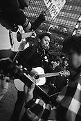 Young men singing protest songs and play guitars outside the American embassy during anti-America and anti-Iraq war demonstrations.