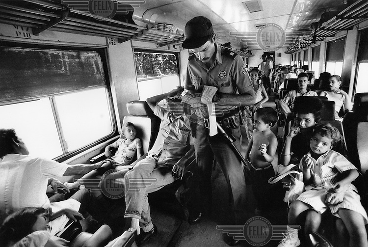 Policeman checks tickets and documents on a train travelling thorugh central Cuba.