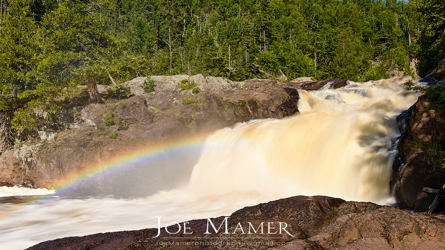 Light refracted in the spray of the waterfall creates a rainbow.