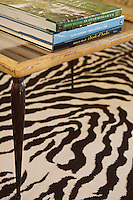 Detail of the corner of a wooden coffee table on a zebra-print rug