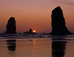 Silhouetted rock formations the Needles with sun orange ball at sunset Cannon Beach Northern Oregon Coast Oregon State USA