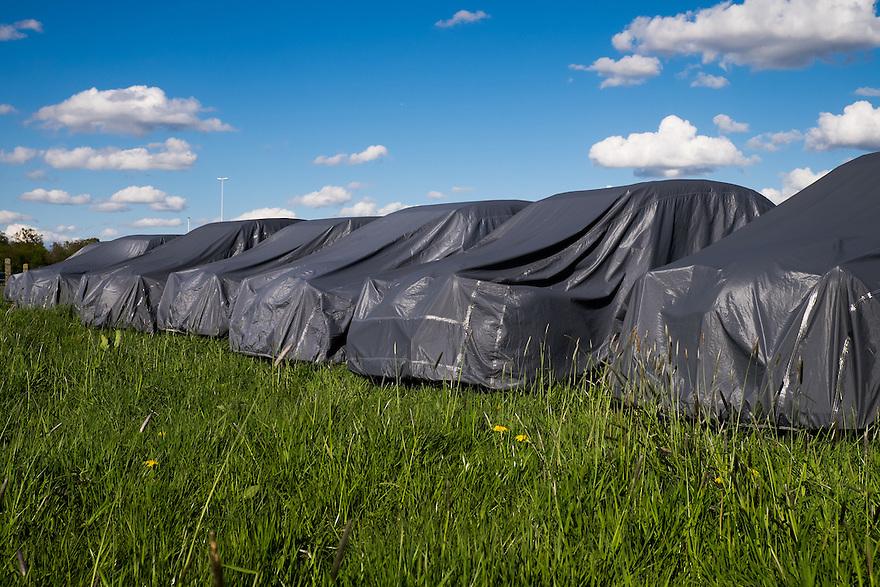 Nederland, Bunnik, 30 april 2015<br /> Rij auto's onder een hoes in een grasveld. De grijze hoezen maken het geheimzinnig wat voor bijzonder auto's dit zijn. Het zijn oude eenden, deuxcheveaux, citroen. <br /> <br /> Foto: Michiel Wijnbergh