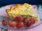 A quiche and some grapes sits on a clear glass plate.