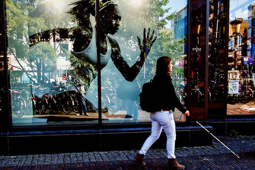 Nederland, Utrecht, 2 sep 2014<br /> Blinde vrouw op straat, loopt langs reclamefoto van kledingwinkel<br /> Foto: (c) Michiel Wijnbergh