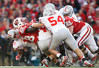 The Ohio State Buckeyes defense takes down Wisconsin Badgers running back Montee Ball (28) in the first quarter of the NCAA football game at Camp Randall Stadium in Madison, WI, Saturday November 17, 2012. The Ohio State Buckeyes defeated the Wisconsin Badgers in overtime 21 - 14. (The Columbus Dispatch / Eamon Queeney)