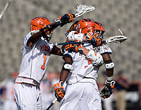 Steele Stanwick (6) of Virginia celebrates a goal with teammate Rhamel Bratton (3) and Shamel Bratton (1) during the ACC men's lacrosse tournament finals in College Park, MD.  Virginia defeated Maryland, 10-6.