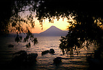A volcano at dusk across Lago Atitlan from the lakefront of Panachel, Guatemala.  The lake is home to several small towns frequented by tourists and, typically, accessed by shuttle boats that criss-cross the lake.