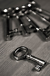 Bunch of old antique brass keys on a table black and white