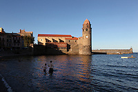 Eglise Notre Dame des Anges, Collioure, France, seen from the sea with bathers in the foreground near the Boramar Beach. The bell tower was converted from a medieval lighthouse and the Mediterranean Gothic style nave was built in 1684. The dome was added to the bell tower in 1810. Picasso, Matisse, Derain, Dufy, Chagall, Marquet, and many others immortalized the small Catalan harbour in their works. Picture by Manuel Cohen.