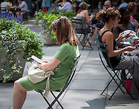 A visitor to Bryant Park in New York uses her Amazon Kindle ereader on Wednesday, July 31, 2013.  (© Richard B. Levine)