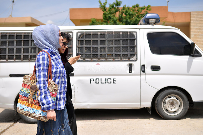 ERBIL, IRAQ: Rezan leaves the Erbil detention center with a social worker after screening cases for representation.  The police vehicle was used to take a female detainee to court to testify about her husband's murder.
