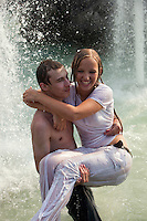 Moscow, Russia, 16/07/2010..A young man carries his girlfriend in fountains next to the Kremlin and Red Square during a prolonged heatwave that has seen temperatures of over 37C, a record for the city.