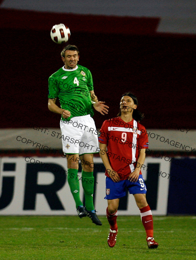 Northern Ireland national football team player McAuley Gareth (4) clears the ball while Serbian Marko Pantelic (9) watces during UEFA Euro 2012 group C qualifying football match Serbia vs Northern Ireland in Belgrade, Serbia, Friday, March 25, 2011. (photo: Pedja Milosavljevic / SIPA PRESS)