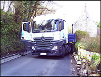 BNPS.co.uk (01202 558833)<br /> Pic: SaveDinahsHollow/BNPS<br /> <br /> A sleepy Dorset village is getting jammed up to 18 times a week with big lorries after highways officials deliberately directed them to drive through it in a controversial traffic experiment.<br /> <br /> The 'unbelievable' strategy has brought havoc and misery to Melbury Abbas where villagers are getting used to the sight of a 30 tonne HGV blocking the narrow main road.<br /> <br /> Cars heading through the pretty hamlet face delays of up to an hour whenever a hapless trucker attempts to pass another large vehicle using the C13.<br /> <br /> Kerbs, grass verges and a water hydrant have been badly damaged by truckers mounting them to create space to squeeze though, while one HGV came within just 2ins of colliding with a Grade II listed property on one occasion.