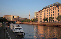 Friedrichstrasse Bahnhof, a mainline and underground train station in Berlin, seen from the Schiffbauerdamm on the bank of the river Spree, Berlin, Germany. In the distance is the Fernsehturm or TV Tower near Alexanderplatz. Picture by Manuel Cohen