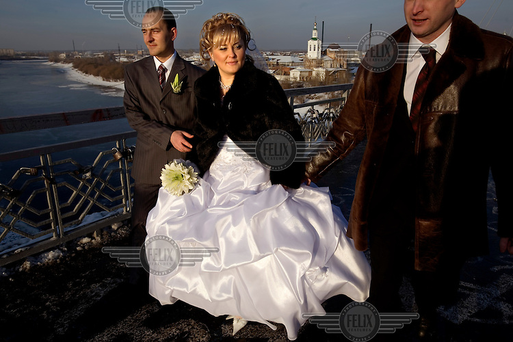 A couple getting married on a bridge in Tyumen. The Siberian city is enjoying an economic boom due to its oil and gas reserves, with living standards of residents second only to those in the capital.