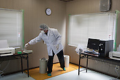 At the seafood radiation testing centre, Haga Noriaki conducts checks for radiation contamination on the octopus and whelks which have been landed that day at the newly and partially reopened fish market landing area of Matsukawaura, in Soma, Japan, on Monday 23 July 2012. The testing centre is located beside the fish market landing area. Once the seafood has been landed it undergoes checks for radiation contamination, and should the seafood pass those checks it will be on sale within the local area within 2 days.