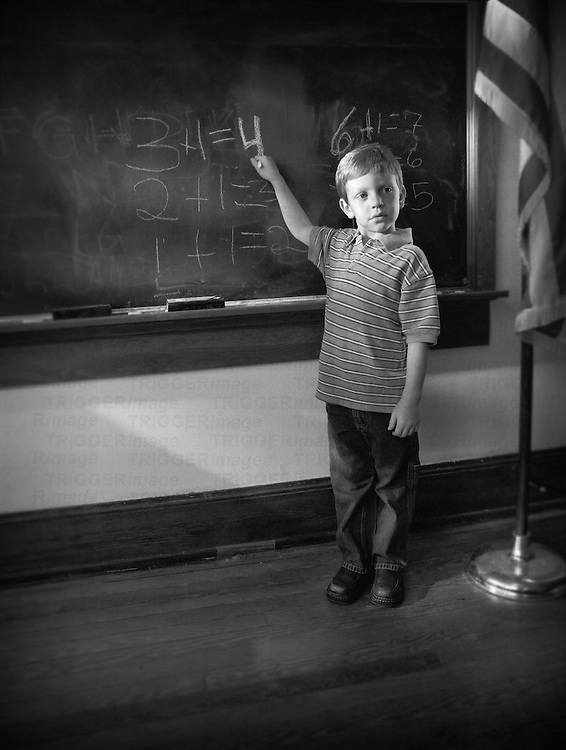 A young boy stands at the chalkboard showing his math class what he has learned