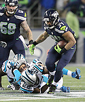Seattle Seahawks running back Thomas Rawls (34) breaks the tackles of Carolina Panthers free safety Michael Griffin (22),  outside linebacker A.J. Klein (56) and defensive tackle Kyle Love (77) on his way to a 13-yard gain in the third quarter at CenturyLink Field in Seattle, Washington on December 4, 2016.  Rawls ran for 105 yards on 16 carries and scored two touchdowns in the Seahawks 40-7 win over the Panthers.  ©2016. Jim Bryant photo. All Rights Reserved.