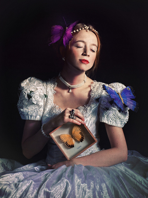 A woman in a white bridal or period gown, with a pearl necklace and butterfly brooches decorating her outfit, holding a framed butterfly, with a gentle dreamy expression.