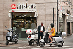 A man and woman on motorcycles outside of a corner cafe in Turin, Italy