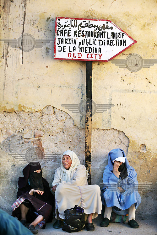 Three women sitting beneath a sign pointing the way to a restaurant in the medina of Fes. It is believed to be the largest contiguous car-free urban area in the world and is a UNESCO World Heritage Site. .