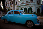 ritzy vintage blue car in front of nice house