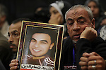 A relative of a killed man in the 'Port Said Massacre' holds his picture during the trial of suspects in Cairo on December 23, 2014. The defendants were originally given sentences ranging from 15 years to life in prison. They were convicted of the murder of over 70 Ahly fans, nine security personnel and three officials from Al-Masry Club at a football match in Port Said in February 2012. Photo by Amr Sayed
