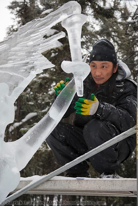 "Mongolian sculptors Rashaanjav Tuvshintur and Tserendash Batmunkh work on the abstract single block sculpture titled ""Evolution"" for the 2009 World Ice Art Championships in Fairbanks, Alaska."