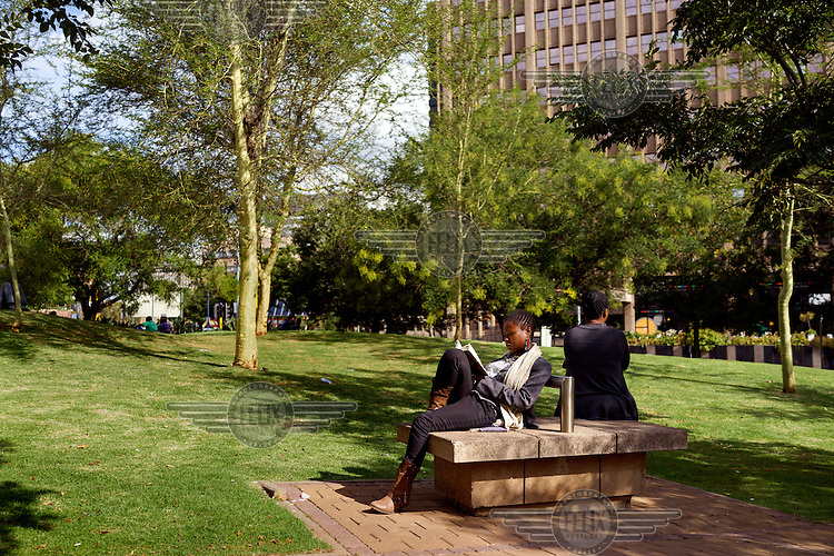 Lungile Zakwe, a management consultant, reading a novel during a break from work in Braamfontein, an inner-city neighbourhood in Johannesburg. Only a few minutes' walk from the poverty, overcrowding and drugs of Hillbrow, Braamfontein features manicured green spaces, upmarket boutiques and restaurants, and is home to the Joburg Theatre and the Joburg Ballet. Inner-city Johannesburg is characterised by such contrasts.