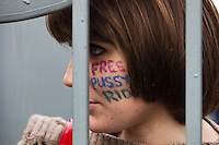 Moscow, Russia, 01/10/2012..A Pussy Riot supporter refused entry to Moscow City Court precincts stares in through security bars from outside. Supporters and opponents of band members Maria Alyokhina, Yekaterina Samutsevich and Nadezhda Tolokonnikova demonstrated outside the court as the three appealed against their two-year jail sentence for their performance in the Christ The Saviour Cathedral. The appeal was postponed until October 10th after Samutsevich fired her lawyer.