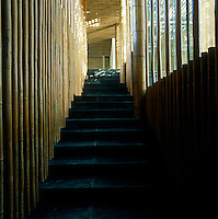 A view up a slate staircase flanked by a bamboo wall and a floor-to-ceiling window