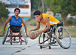 Roel Hernandez dribbles the basketball while pushing his wheelchair forward during practice in Zipolite, a town in Oaxaca, Mexico.  Behind him is Bartolome Martinez. They play on the Oaxaca Costa wheelchair basketball team.