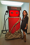 Massapequa, New York, USA. September 18, 2014. LORI HOROWITZ, artist and gallery owner, is standing next to her sculpture Distilled Life, a glowing red gas pump with FOSSIL written at top, during the Studio 5404 Art Space opening reception for the art show Taking it to the Street. Environment is the theme of the mixed media installation, which is made of wood, plastic, and paper mache, and the exhibit features new works by emerging and up-and-coming local and New York artists. Studio 5404 is on the South Shore of Long Island.