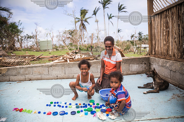 Celina Amos, 39, the Head Teacher of St Martin kindergarten, plays with pre-school pupils Paloma (five, left) and Luisa (three, right). Their kindergarten was destroyed by Cyclone Pam on 13 March 2015.