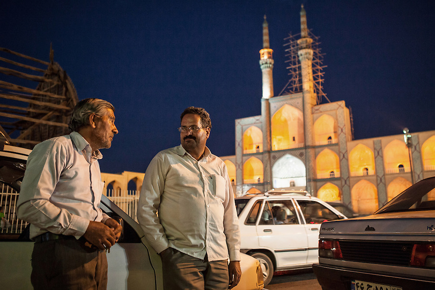 Taxi driver and Amir Chakhmakh Complex in the backgound. The building which used for Shia Ashura commemoration is one of the largest hosseiniyeh in Iran.