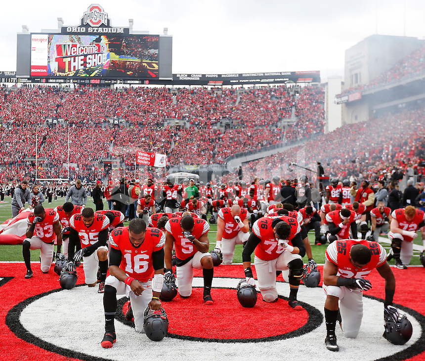 Ohio State Buckeyes quarterback J.T. Barrett (16) and his teammates kneel in prayer prior to the NCAA football game between the Ohio State Buckeyes and the Michigan Wolverines at Ohio Stadium on Saturday, November 26, 2016. (Columbus Dispatch photo by Jonathan Quilter)