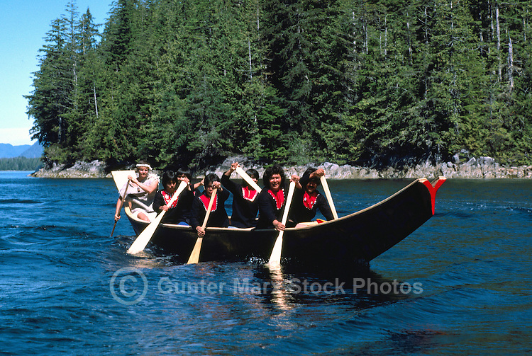 Native American Indians canoeing in a Traditional Dugout Canoe near Bella Bella, on the West Coast of British Columbia, Canada