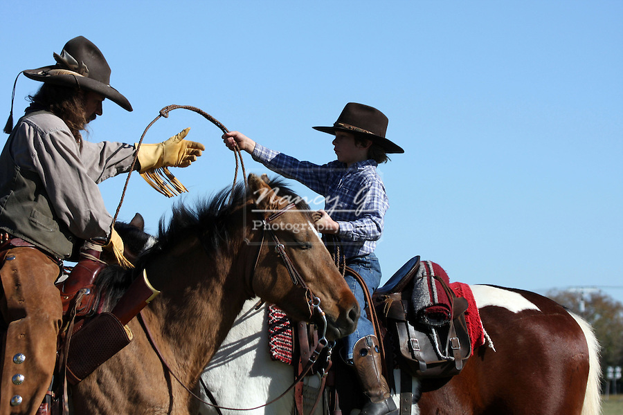 A cowboy father on horseback showing his son how to throw a rope to catch cattle
