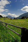 Fenced field in the spring agaist background of mountains and alpine homes. Pitztal Valley, Tyrol,Tirol, Austria.