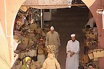 An archway crowded with baskets and people leads to more streets in the markets of Marrakesh, Morocco