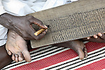 A man writes out portions of the Koran in the Dereig Camp for internally displaced persons, one of many such settlements for people displaced by the violence in Darfur.