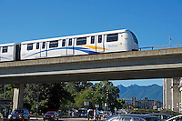 The Skytrain elevated light rapid transit system crossing over a busy street, Vancouver, BC, Canada