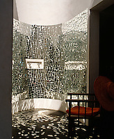 Light reflects off the shards of mirror which cover the curved walls and dances across the floor of this unusual shower