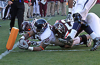 Nov 27, 2010; Charlottesville, VA, USA; Virginia Cavaliers running back Keith Payne (22) scores a 4th quarter touchdown between Virginia Tech Hokies linebacker Jack Tyler (58) and Virginia Tech Hokies linebacker Tariq Edwards (24) during the game at Lane Stadium. Virginia Tech won 37-7. Mandatory Credit: Andrew Shurtleff-