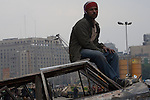 An Egyptian anti-Mubarak protester sits atop a burnt out vehicle near Egyptian Army lines during ongoing protests February 05, 2011 in Tahrir Square in downtown Cairo, Egypt. Overnight the army appeared to tighten its control of the no man's land around the square and made efforts today to convince protesters to leave voluntarily. . .Credit: Scott Nelson